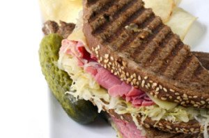 reuben sandwhich photo showing sourdough rye bread, sauerkraut, and corned beef along with a pickle